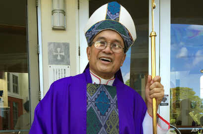 FILE - Archbishop Anthony Apuron stands in front of the Dulce Nombre de Maria Cathedral Basilica in Hagatna, Guam, in November 2014.