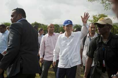 FILE - U.N. Secretary-General Ban Ki-moon, center wearing blue cap, greets residents during the launching of sanitation campaign in Hinche, Haiti, July 14, 2014.
