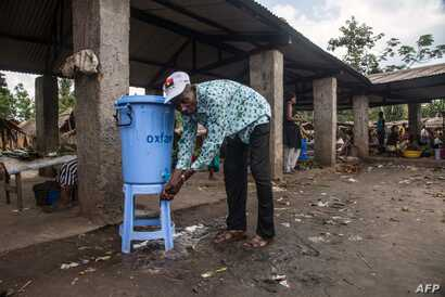 "A man washes his hands with water from a dispenser containing water mixed with disinfectant at the Congo Air Market on the airport road in the east of Mbandaka, DRC, May 23, 2018. An Ebola outbreak in the Democratic Republic of Congo has a clear ""po..."