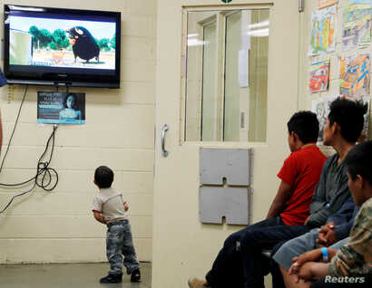 A detained immigrant child watches a cartoon while awaiting the arrival of U.S. first lady Melania Trump with other young detained immigrants at a U.S Customs and Border patrol immigration detainee processing facility in Tucson, Arizona, June 28, 201...