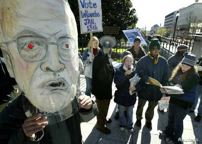 FILE - Supporters of Democratic presidential nominee Lyndon Larouche, including one wearing a mask lampooning Vice President Dick Cheney, protest outside the Old Executive building near the White House in Washington, Dec. 1, 2003.