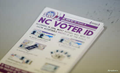 """A pile of government pamphlets explaining North Carolina's controversial """"Voter ID"""" law sits on table at a polling station."""