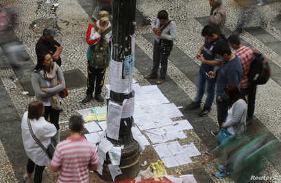 People look at a list of job offers posted in a main street in downtown Sao Paulo, Aug. 13, 2014.