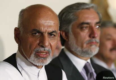 FILE - Afghanistan's presidential candidate Ashraf Ghani (L) speaks with rival candidate Abdullah Abdullah (R) at his side during a news conference in Kabul, July 12, 2014.