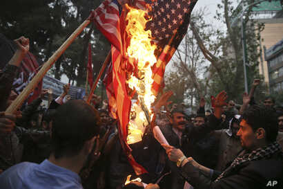 Hardline Iranian demonstrators burn representations of the U.S. flag during a gathering in front of the former U.S. Embassy in Tehran, Iran, Wednesday, May 9, 2018, reacting to President Donald Trump's decision to pull out of the nuclear deal and ren