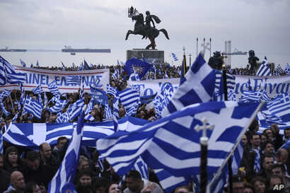 "Greek protesters wave flags and banners during a rally against the use of the term ""Macedonia"" for the northern neighbouring country's name, at the northern Greek city of Thessaloniki on Sunday, Jan. 21, 2018."