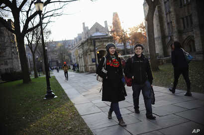 FILE - Yale University sophomore Yupei Guo, left, walks with friend Joseph Lachman on the school's campus in New Haven, Conn., In Nov. 20, 2014. With more undergraduates coming from overseas than ever, some Ivy League universities are reaching out in...