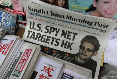 A copy of the South China Morning Post newspaper, carrying the latest interview with Edward Snowden, is displayed on a newspaper stand along with local Chinese newspapers, in Hong Kong, June 13, 2013.
