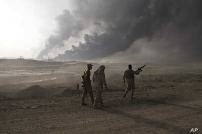 Iraqi army soldiers man a checkpoint as oil wells burn on the outskirts of Qayyarah, Iraq, Oct. 19, 2016.