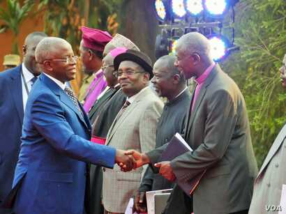 Presidential aspirant and former Prime Minister Amama Mbabazi arrives at the debate in Kampala, Feb. 13, 2016, greeted by the Inter-Religious Council of Uganda.