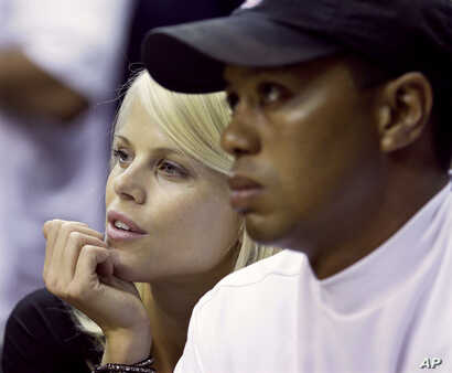 In this June 11, 2009 file photo, Elin Nordegren talks to her husband, golfer Tiger Woods, during the first quarter of Game 4 of the NBA basketball finals in Orlando, Fla.