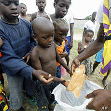 A man distributes bread to children at Abidjan's St. Ambrose church, a temporary refuge for people who fled from clashes between forces loyal to incumbent president Laurent Gbagbo and his rival Alassane Ouattara (File Photo)