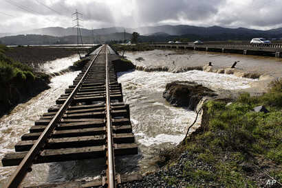Water from recent heavy rain storms breeched a levee and flows under railroad tracks in Novato, Calif., Feb. 14, 2019.