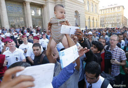 Migrants wave their train tickets and lift up children outside the main Eastern Railway station in Budapest, Hungary, Sept. 1, 2015.