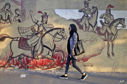 An Iranian woman walks past paintings of a Persian poetry in downtown Tehran, Iran, Monday, July 30, 2018. Iran's currency has dropped to a record low ahead of the imposition of renewed American sanctions, with many fearing prolonged economic sufferi...