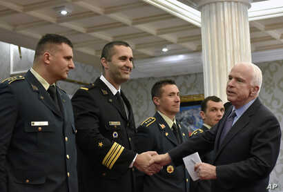 U.S. Sen. John McCain, right, shakes hand with Montenegrin army officers in Podgorica, Montenegro, April 12, 2017.