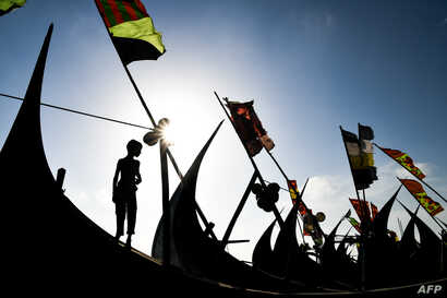 A Rohingya refugee boy looks on as he stands on a fishing boat at Shamlapur camp in Teknaf.