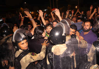 Iraqi riot police prevent protesters from storming the provincial council building during a demonstration in Basra, 550 kilometers (340 miles) southeast of Baghdad, Iraq, May 21, 2016.