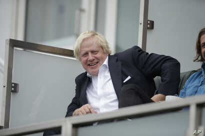 Britain's former Foreign Secretary Boris Johnson reacts to seeing photographers taking his picture as he sits in a spectator seat whilst attending the fifth cricket test match of a five match series between England and India at the Oval cricket groun...
