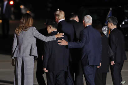 First lady Melania Trump and Vice President Mike Pence put their arms around North Korean detainee Tony Kim as they walk with President Donald Trump, Secretary of State Mike Pompeo, Kim Dong Chul, and Kim Hak Song as they leave Andrews Air Force Base...
