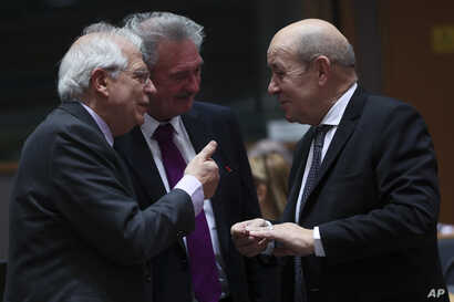 French Foreign Minister Jean-Yves Le Drian, right, speaks with Spanish Foreign Minister Josep Borrell, left, and Luxembourg's Foreign Minister Jean Asselborn during an EU Foreign Ministers meeting at the European Council headquarters in Brussels, Bel...