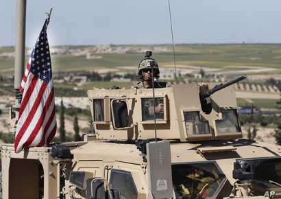 FILE - A U.S. soldier sits atop an armored vehicle, in Manbij, Syria, April 4, 2018.