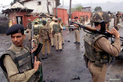 FILE - Indian Border Security Force troopers stand guard near the scene of a car bomb explosion outside the Jammu and Kashmir Legislative Assembly building in the heart of Srinagar, Oct. 1, 2001.