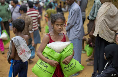 A newly arrived Rohingya girl carries food rations in Kutupalong, Bangladesh, Saturday, Sept. 30, 2017.