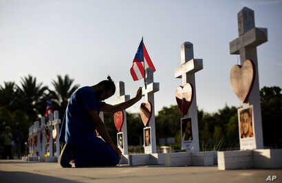 Ernesto Vergne prays at a cross honoring his friend Xavier Emmanuel Serrano Rosado and the other victims at a memorial to those killed in the Pulse nightclub mass shooting a few blocks from the club in Orlando, Florida, June 17, 2016.