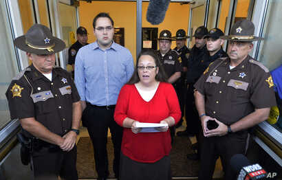 Flanked by Rowan County Sheriff's deputies, Rowan County Clerk Kim Davis, center, with her son Nathan Davis standing by her side, makes a statement to the media at the front door of the Rowan County Judicial Center in Morehead, Kentucky, Sept. 14, 20...