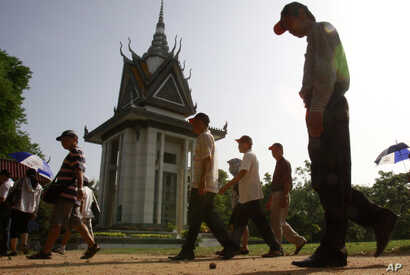 FILE - Foreign tourists walk through Choeung Ek stupa, which stores thousands of human bones and skulls of the Khmer Rouge's victims in the outskirt of Phnom Penh, Cambodia, June 25, 2011.