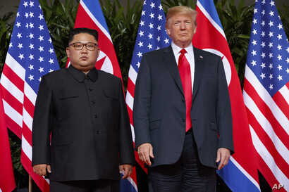 FILE - U.S. President Donald Trump, right, meets with North Korean leader Kim Jong Un on Sentosa Island, in Singapore, June. 12, 2018. North Korea warned Friday it could revive a state policy aimed at strengthening its nuclear arsenal if the United S