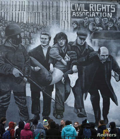 Tourists stand in front of a mural depicting the Bloody Sunday events, in Londonderry, Northern Ireland, March 14, 2019.