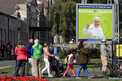 People walk past a poster of Pope Francis outside the Pastoral Congress at the World Meeting of Families in Dublin, Ireland, Aug. 24, 2018.
