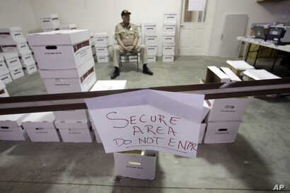 FILE - A security guard stands watch over ballots in a secured area during the write-in ballot count, Nov. 11, 2010, in Juneau, Alaska.