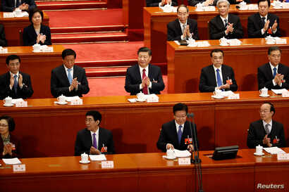 Chinese President Xi Jinping, Chinese Premier Li Keqiang and other officials applaud at the second plenary session of the National People's Congress (NPC) at the Great Hall of the People in Beijing, China March 9, 2018.