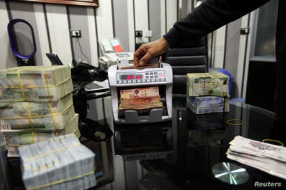 A man uses a currency counting machine to count Libyan dinars at a currency exchange office in Tripoli, April 27, 2016.
