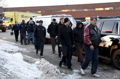 Employees are escorted from the scene of a shooting at a manufacturing plant, Feb. 15, 2019, in Aurora, Ill.