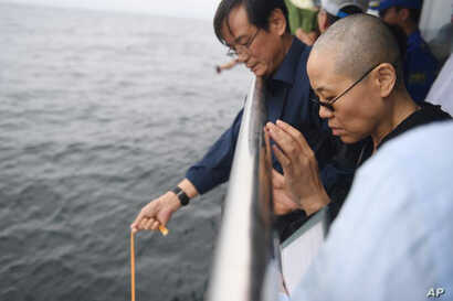In this photo provided by the Shenyang Municipal Information Office, Liu Xia, the wife of Chinese Nobel Peace Prize laureate Liu Xiaobo, watches as Liu's ashes are buried at sea off the coast of Dalian in northeastern China's Liaoning Province, July ...