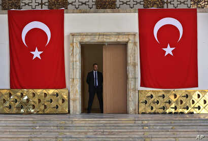A Turkish parliament security man stands guard next to the broken yellow copper doors laid on the ground at the entrance of the assembly hall at the parliament building which was attacked by the Turkish warplanes during the failed military coup last ...