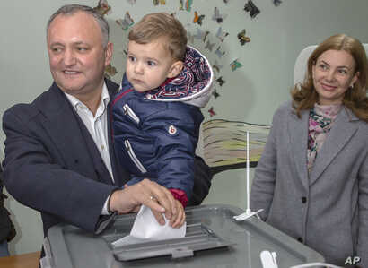 FILE - Leader of the Socialists Party, Igor Dodon, shown with his son Nikolai and wife Galina, casts his ballot, during the presidential elections in Chisinau, Moldova, Oct. 30, 2016. Dodon and second-place finisher Maia Sandu will face off in a Nove...
