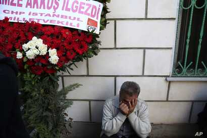 A man cries under a wreath during the funerals of victims on Saturday's bombing attacks, in Istanbul, Oct. 12, 2015.