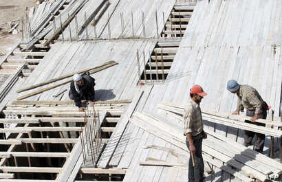 FILE - Members of a construction crew work at a site for new appartment buildings in Damascus, Syria.