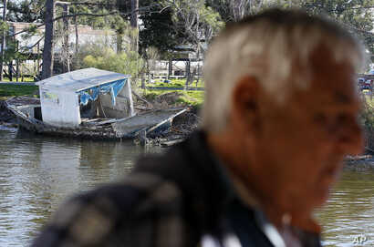 FILE - An abandoned fishing boat is seen sitting on the bank of a bayou past seafood dock owner Price Billiot in the Native American fishing village of Pointe-Aux-Chenes, La., devastated after a 2010 oil spill in the Gulf of Mexico. Even before the s...