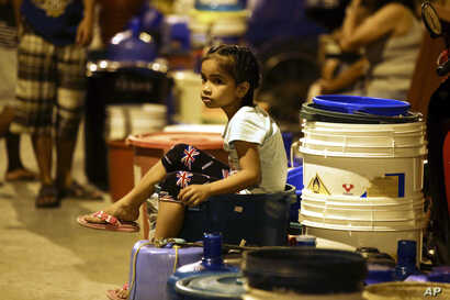 A Filipino girl waits for trucks bearing water after supply has been out for the past days in Mandaluyong, metropolitan Manila, March 14, 2019.