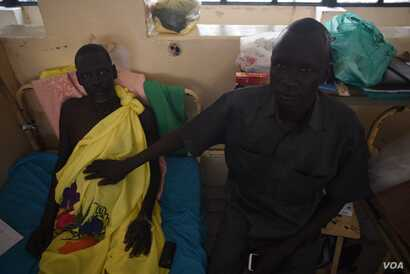 Michael Chieng Bol, right, holds his hand on his brother Simon's stomach, which is in need of further surgery following an operation to remove his appendix, in Juba Teaching Hospital, South Sudan's largest medical facility, May 23, 2016. (J. Patinkin...