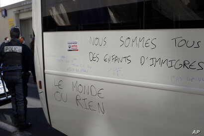 """France Migrants: Police officer walks by a graffiti reading """"We Are All Migrants' Children, The World or Nothing"""" after they evacuate migrants camped out in the empty Jean Jaures school in northeast Paris, France, Wednesday, May 4, 2016."""