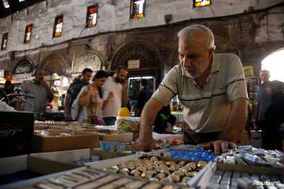 A man inspects sweets ahead of Eid celebrations in al-Bazourieh Souk in Damascus, Syria, Sept. 10, 2016.