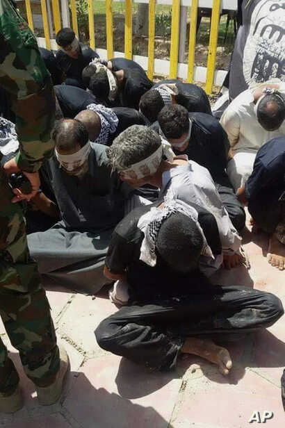 Iraqi security forces and Peace Brigades, a Shiite militia group loyal to Shiite cleric Muqtada al-Sadr, detain 12 fighters of the Islamic State group in Beiji, some 155 miles (250 kilometers) north of Baghdad, Iraq, June 7, 2015.