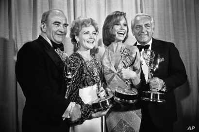 """FILE - Members of """"The Mary Tyler Moore Show"""" pose with their Emmys backstage at the 28th annual Emmy Awards in Los Angeles, May 18, 1976. From left are, Ed Asner, Betty White, Moore and Ted Knight."""